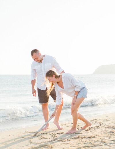 Wedding day couple drawing heart on the sand